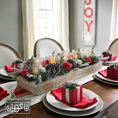 میز شام کریسمس با دستمال سفره قرمز و برگ سبز کاج و میوه کاج