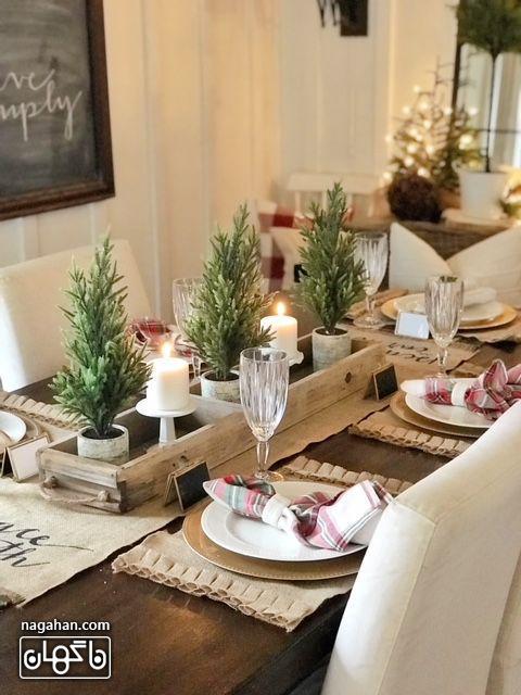 میز شام کریسمس با برگ کاج و شمع