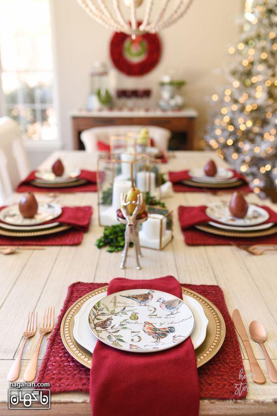 چیدمان شیک میز شام کریسمس با دستمال سفره قرمز و بشقاب طلایی