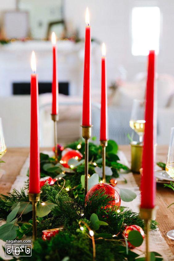 شمع های بلند قرمز در تزیین میز شام کریسمش 2021