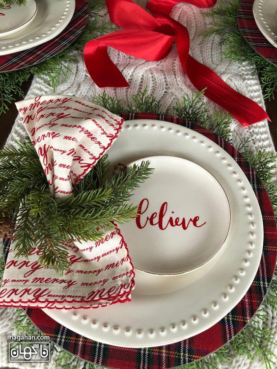 میز شام کریسمس با دستمال سفره و برگ سبز کاج