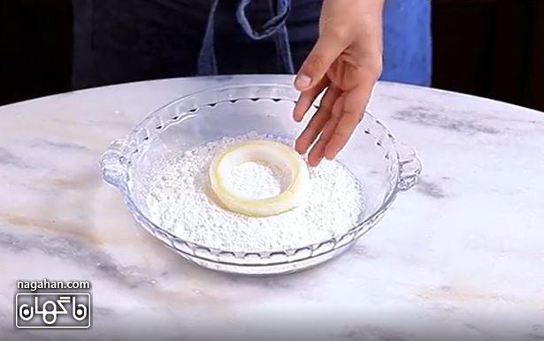 حلقه ها را ابتدا درون آرد گندم غوطه ور کنید.