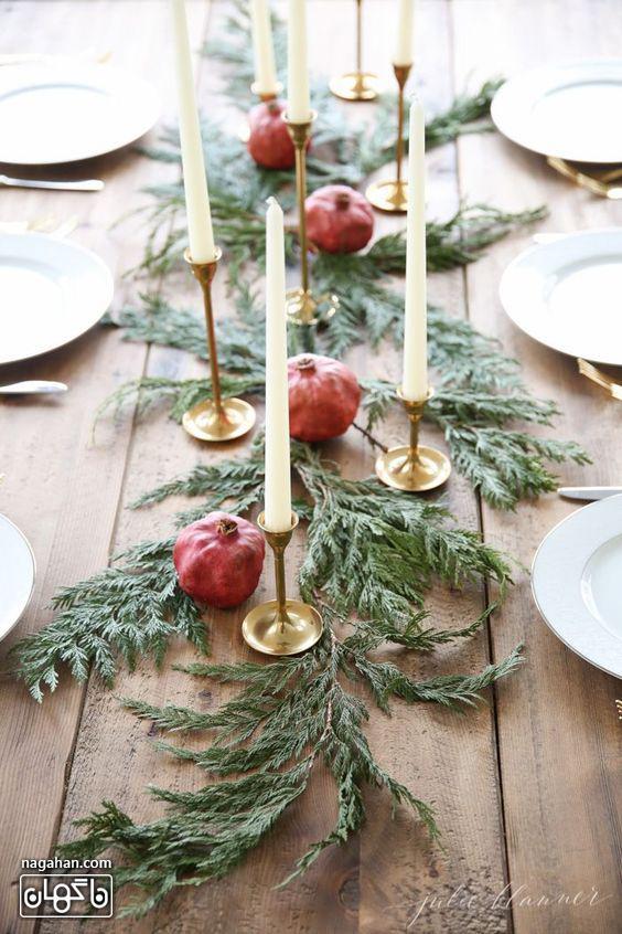چیدن ساده میز کریسمن با انار و برگ درخت کاج